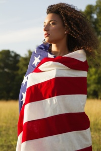 Mixed race woman wrapped in American flag